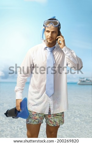 Young businessman on the beach having phone call, wearing shirt and tie and scuba diving equipments. - stock photo
