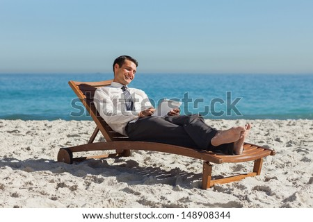Young businessman  on the beach relaxing on a deck chair using his tablet - stock photo