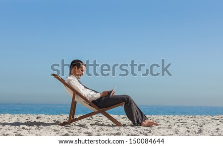 Young businessman on the beach resting on his deck chair using his tablet - stock photo