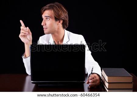 young businessman on the computer on a black background. Studio shot - stock photo