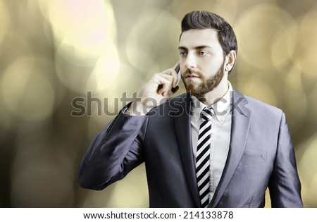 Young businessman on the phone on orange background - stock photo