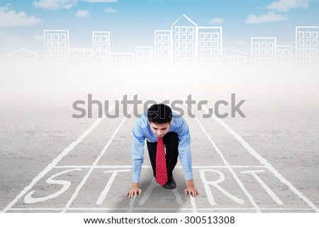Young businessman on the start line with ready position to compete, shot outdoors - stock photo
