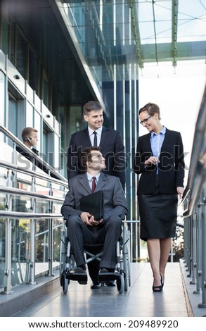 Young businessman on wheelchair and his co-workers, vertical - stock photo