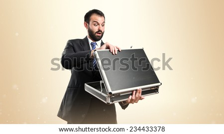 Young businessman open his briefcase over ocher background.  - stock photo