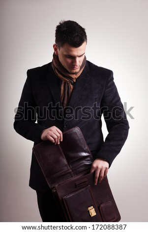 Young businessman opening bag