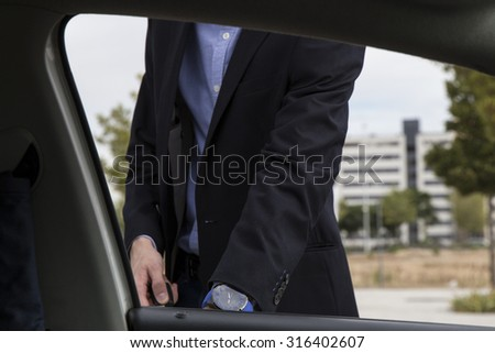 Young businessman opening the door of his car, view from inside