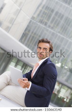 Young businessman outside office holding tablet -