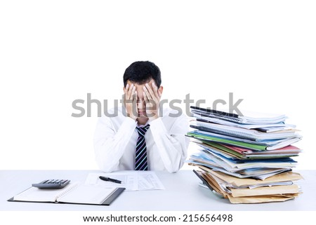 Young businessman overwhelmed with stack of files on the desk - stock photo