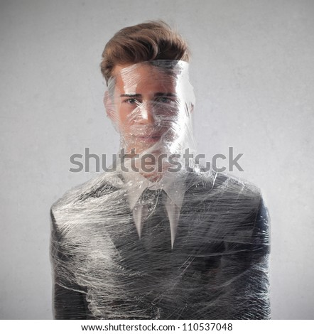 Young businessman packed in plastic wrap - stock photo