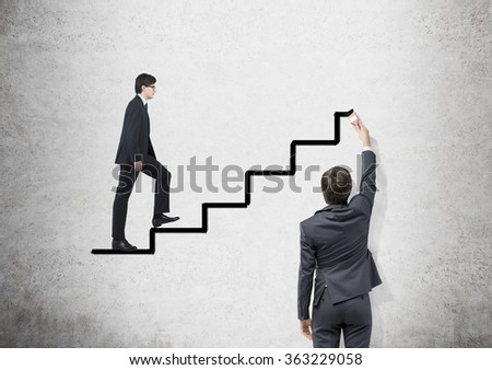 Young businessman painting black stairs with a brush. Young man ascending it.  Concrete background. Concept of career growth.