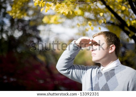 young businessman placing hand above eyebrows looking for something with autumn trees in background - stock photo