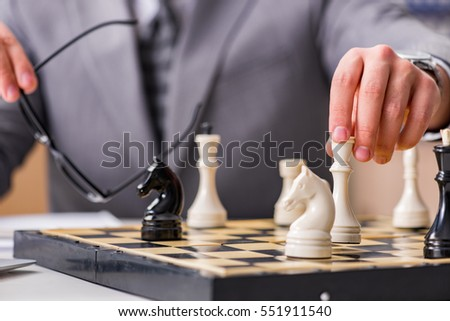 Young businessman playing chess in the office