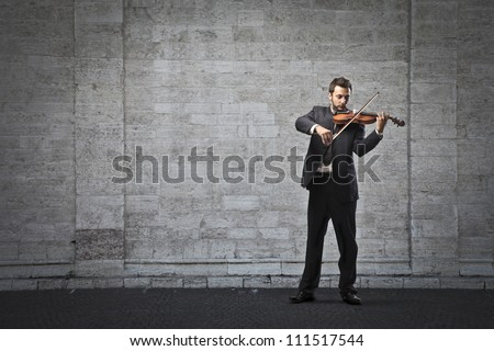 Young businessman playing the violin on a street - stock photo