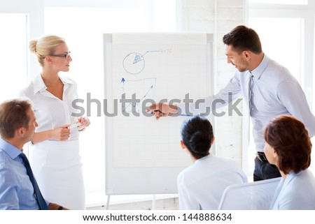 young businessman pointing at graph on flip board in office - stock photo