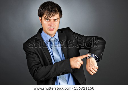 Young businessman pointing to his watch with an angry expression on his face isolated on gray background - stock photo
