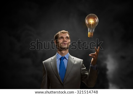 Young businessman pointing with finger at glowing light bulb
