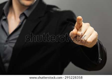 Young businessman pointing with his left hand, isolated on gray