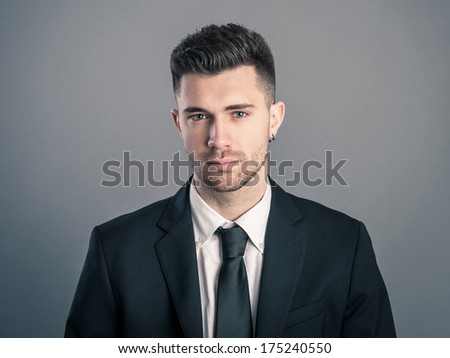 Young businessman portrait against dark background.  - stock photo