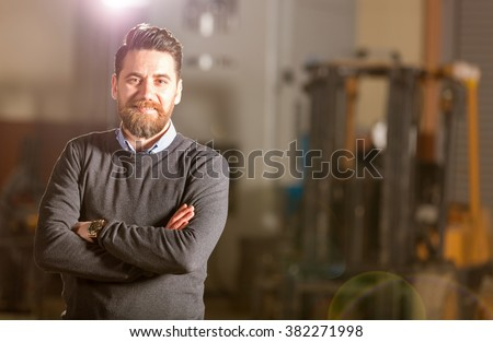 Young businessman posing in factory.