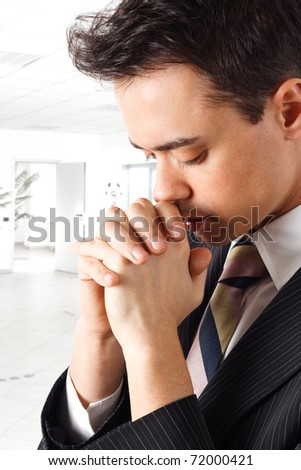 Young businessman praying in an office environment - stock photo