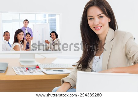 Young businessman presenting figures against female artist at desk with computer in the office - stock photo