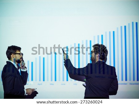 Young businessman presenting his colleague financial report on the wall