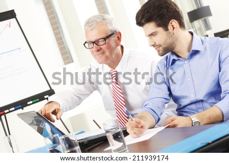 Young businessman presenting his idea while sitting at meeting. Small business. - stock photo