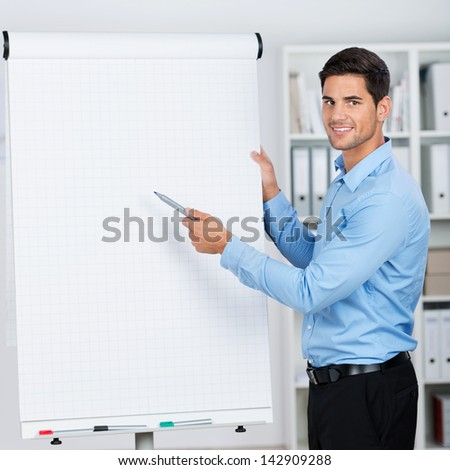 Young businessman presenting important data on a flipchart with smile. - stock photo