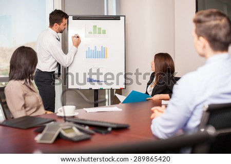 Young businessman presenting some results in a flipboard to a group of people in a meeting room - stock photo