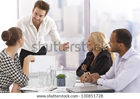 Young businessman presenting to partners in meetingroom.