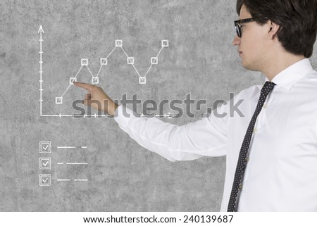 young businessman presses graph on gray wall