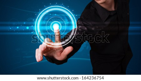 Young businessman pressing high tech type of modern buttons