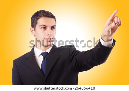 Young businessman pressing virtual buttons - stock photo