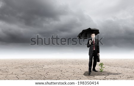 Young businessman protecting little sprout with umbrella