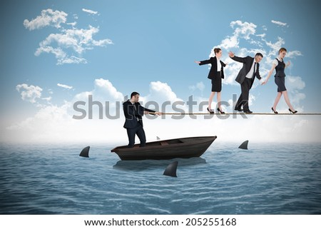 Young businessman pulling a tightrope for business people against sharks circling small boat in the ocean - stock photo