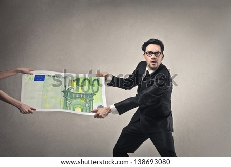 young businessman pulling money - stock photo