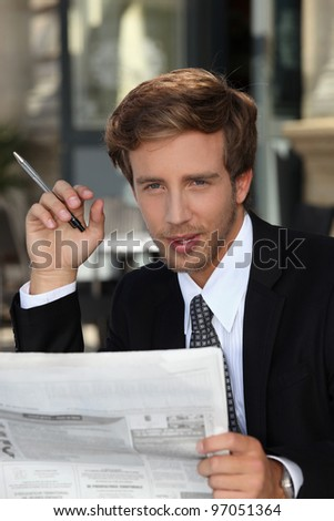 young businessman reading a newspaper - stock photo
