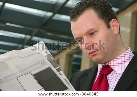 Young businessman reading blank newspapers