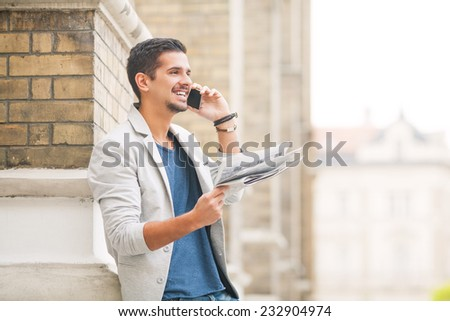 Young businessman reading newspaper and talking on the phone - stock photo