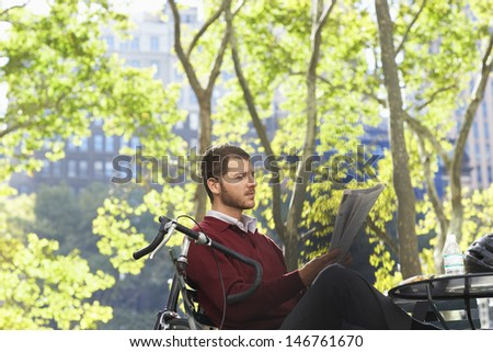 Young businessman reading newspaper in park - stock photo