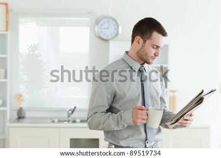 Young businessman reading the news while having breakfast in his kitchen - stock photo