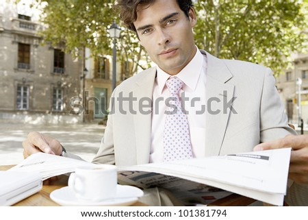 Young businessman reading the newspaper while sitting in a coffee shop's terrace in the city, outdoors. - stock photo