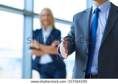 Young businessman ready to handshake standing in office - stock photo