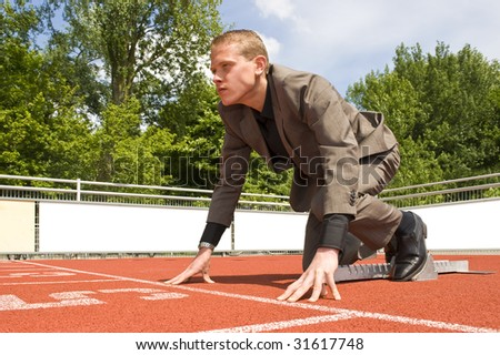 Young businessman, ready to start his career, visualized by getting ready for a sprint run in the starting blocks with a determined look in his eye - stock photo