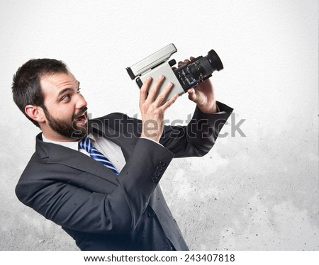 Young businessman recording video over textured background - stock photo
