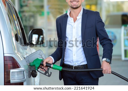 Young businessman refueling car tank at fuel station - stock photo