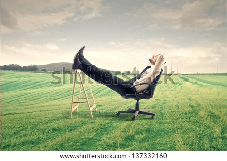 young businessman relaxes sitting outdoor - stock photo