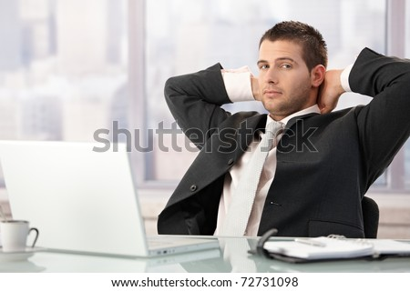 Young businessman relaxing in office, sitting at desk.?