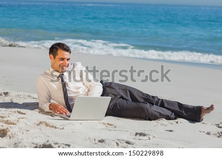 Young businessman relaxing lying on the sand using his laptop - stock photo