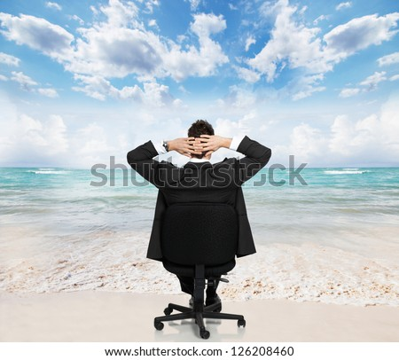 Young businessman relaxing on the beach. Conceptual background. - stock photo